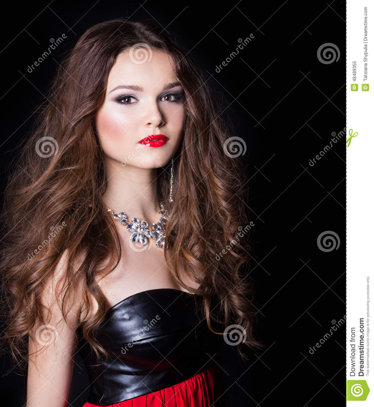 Portrait of a beautiful elegant girl in evening dress with a large necklace with a bright festive makeup Studio