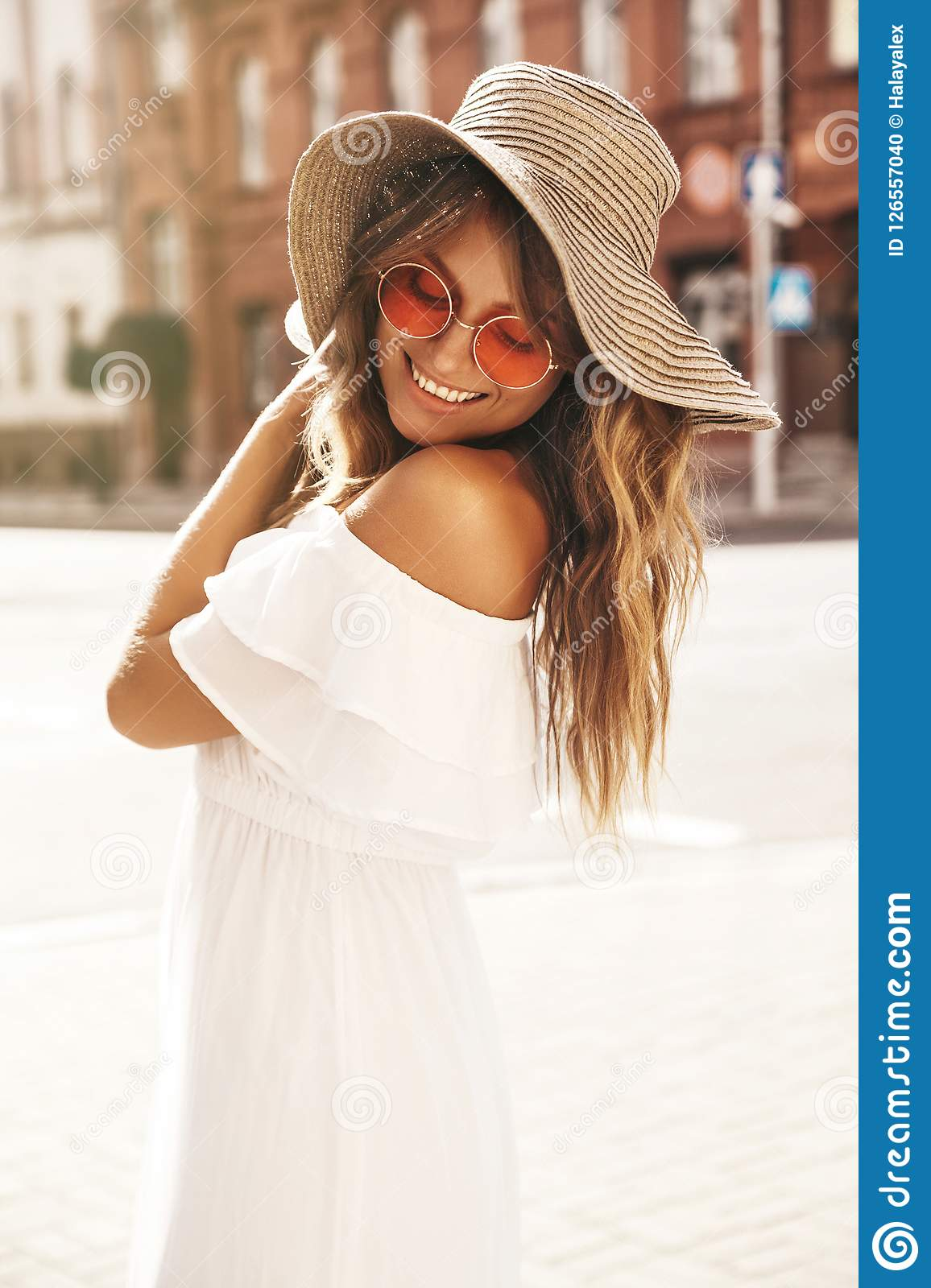 55a39a27c Portrait of beautiful smiling cute blond teenager model with no makeup in  summer hipster white dress and big beach hat posing on the street background