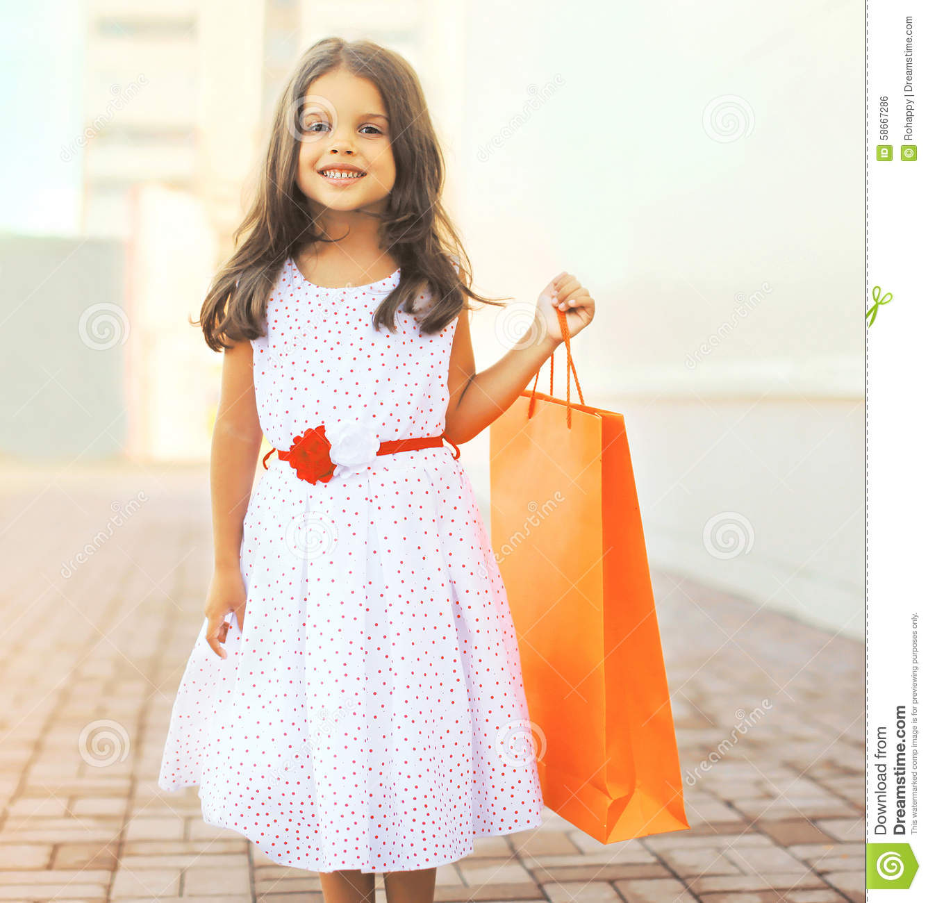 Portrait of beautiful smiling little girl wearing a dress. With shopping  bag outdoors royalty free 1127e2599
