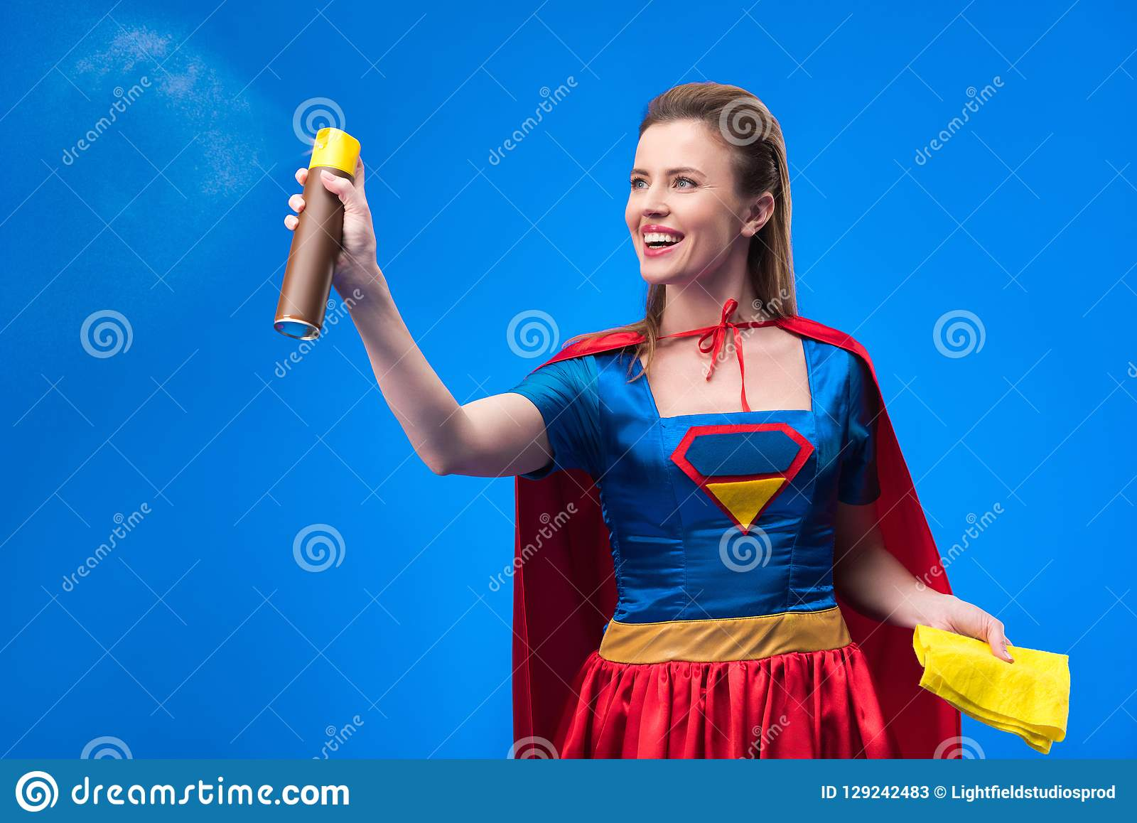 portrait of beautiful smiling superwoman with rag and detergent for cleaning