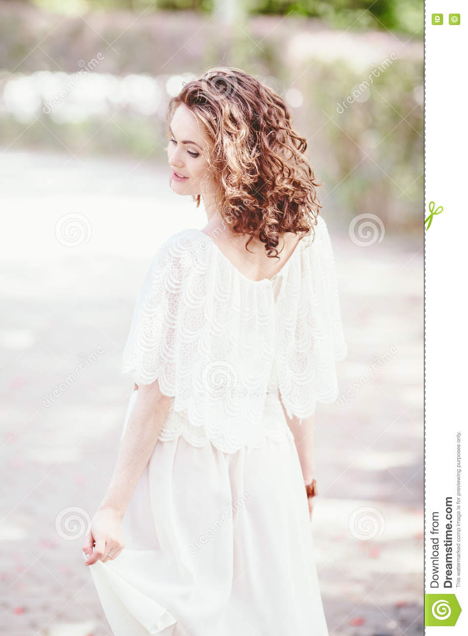 Portrait of beautiful smiling white Caucasian girl woman with long dark red brown hair and hazel eyes, in white summer dress