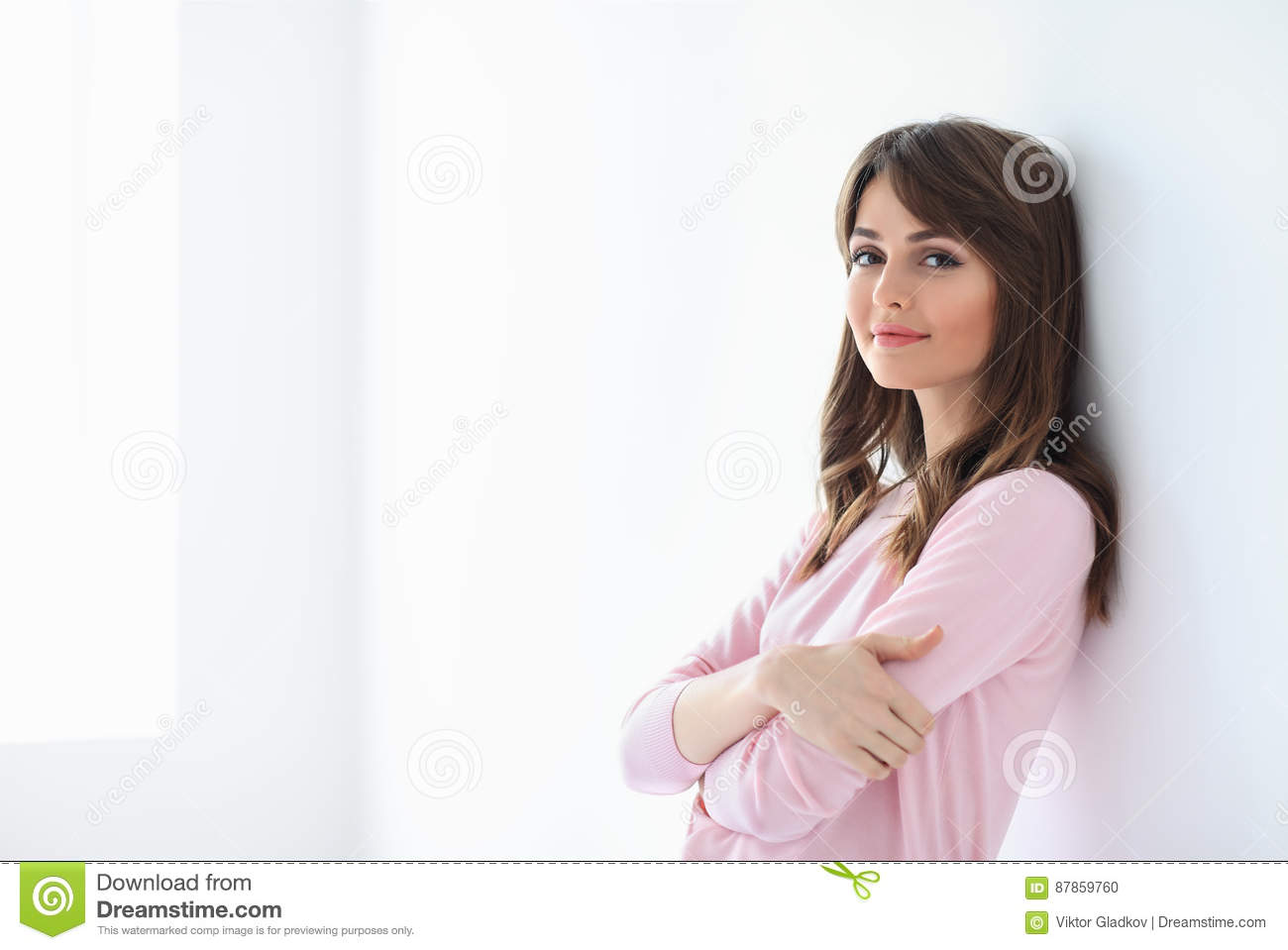 Portrait of beautiful smiling woman with crossed arms on white b