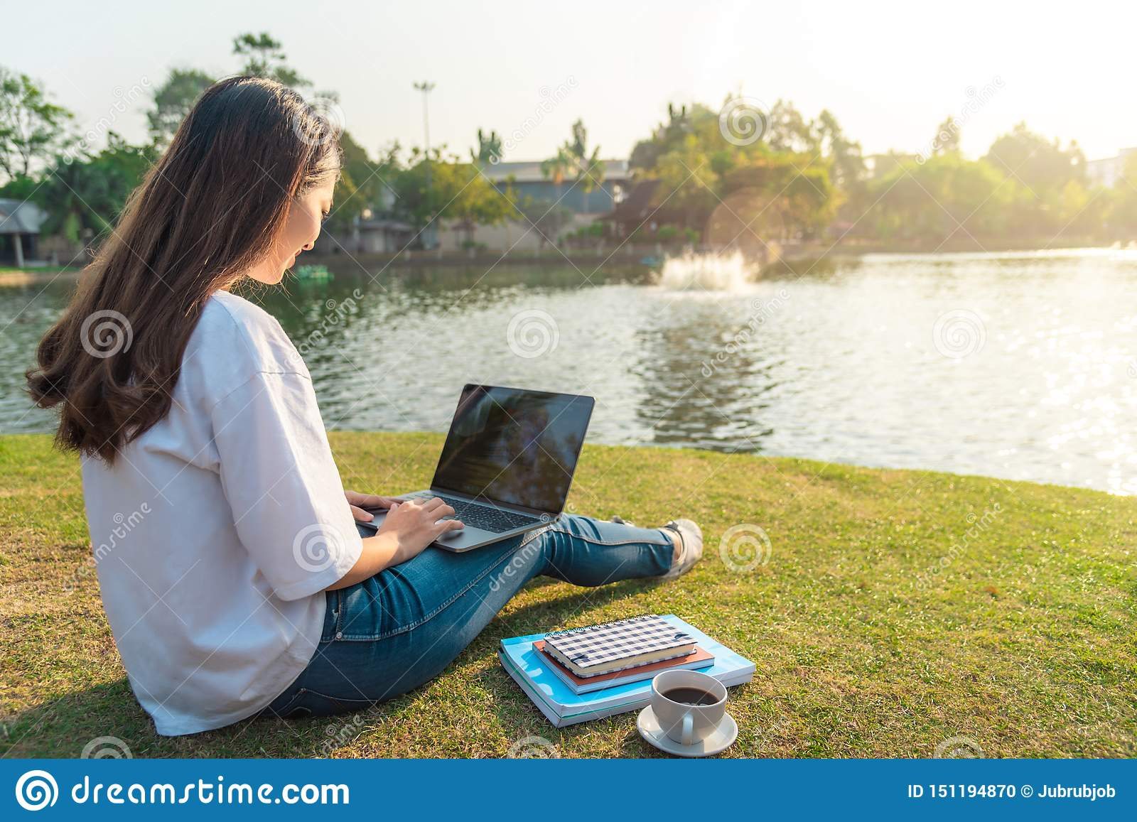 Portrait of beautiful smiling woman sitting on green grass in park with legs crossed during summer day and writing notes with pen