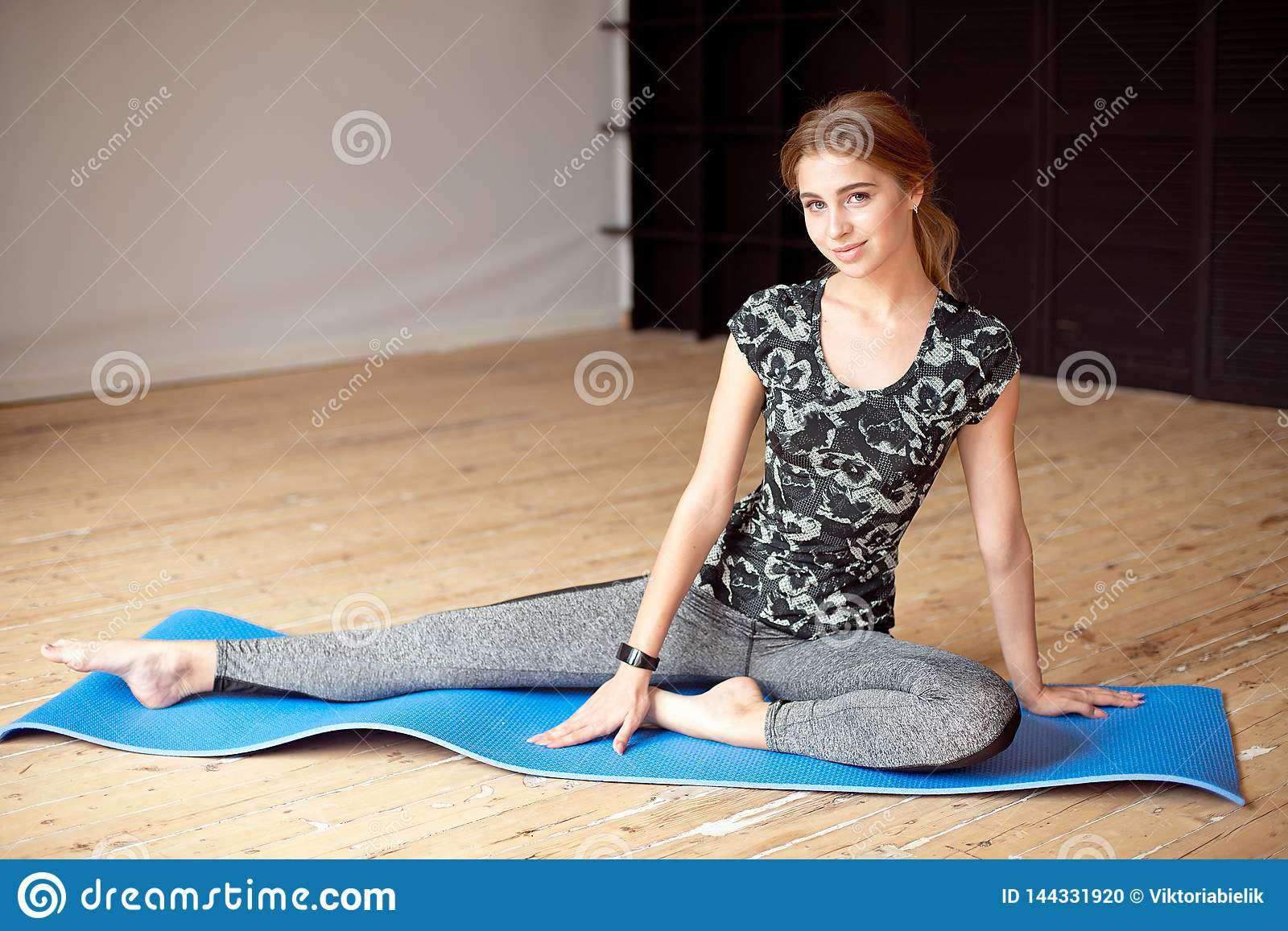 Portrait of a beautiful sports girl in sportswear resting after a fitness workout drinking water from a bottle sitting
