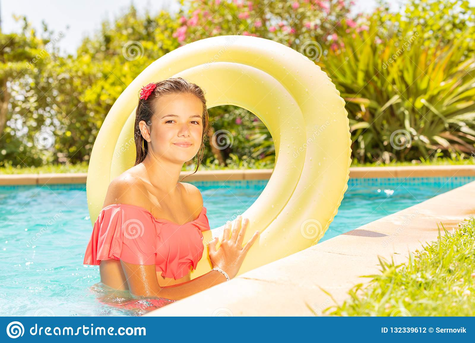 Portrait of beautiful teenage girl wearing bikini standing in outdoor  swimming pool with big yellow swim ring c0662f012