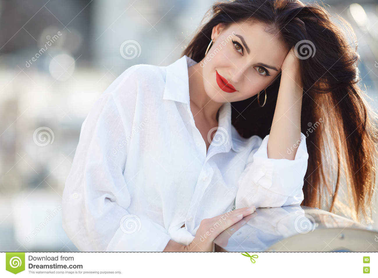 Portrait of a beautiful woman on the background of the sea and yachts