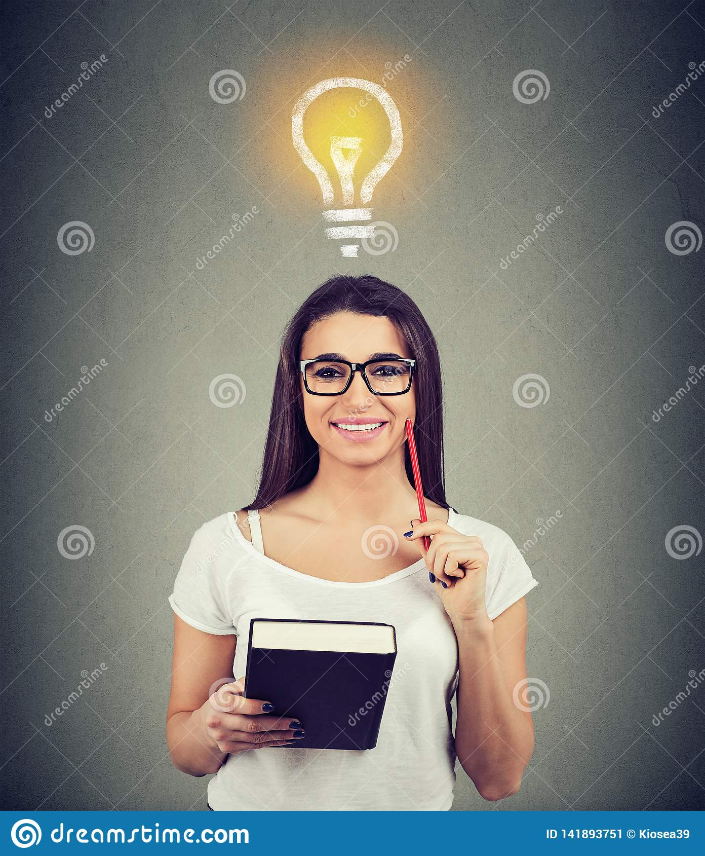 Portrait of a beautiful woman with bright light bulb above head holding a book