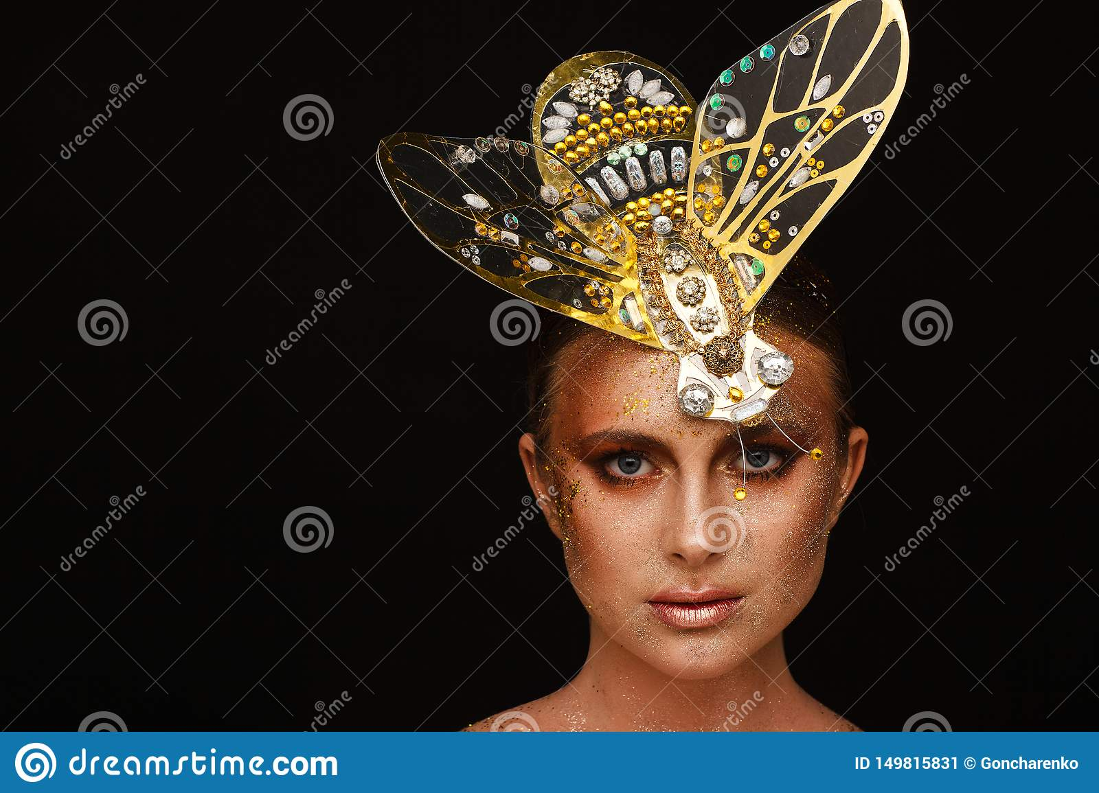 Portrait of a beautiful woman with expressive creative make-up in bronze and with a decoration on her head