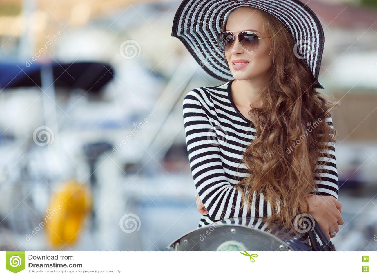 Portrait of beautiful woman in hat on the pier