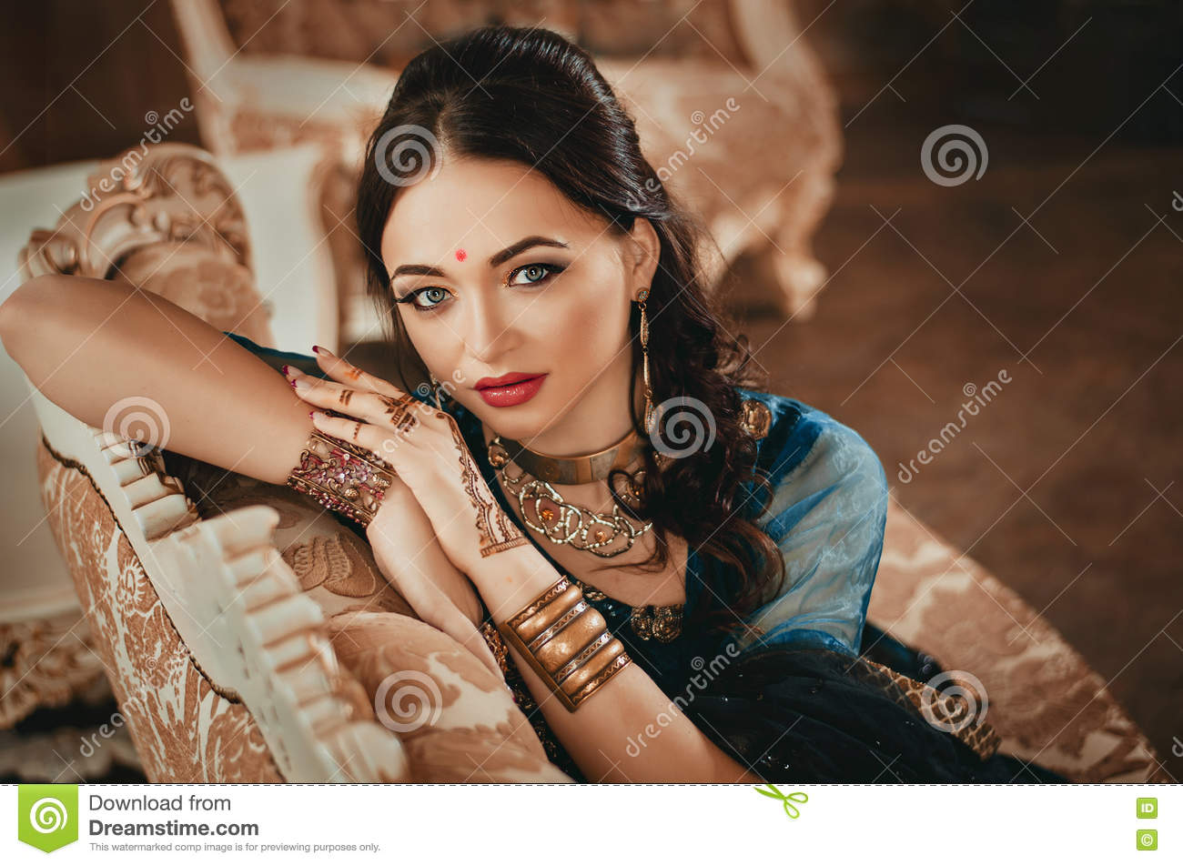 Portrait of a beautiful woman in Indian traditional Chinese dress, with her hands painted with henna mehendi. Girl sitting on a lu