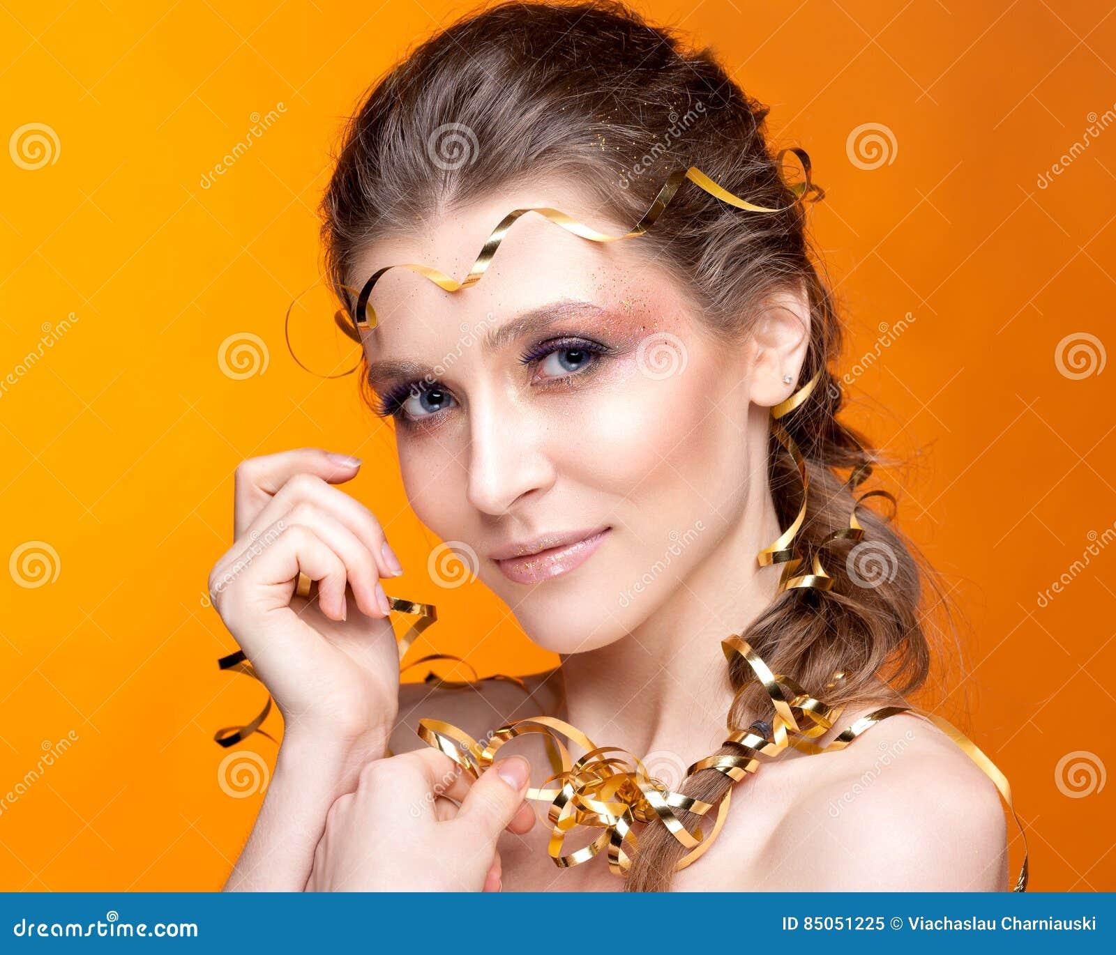Portrait of a beautiful woman on an orange background.