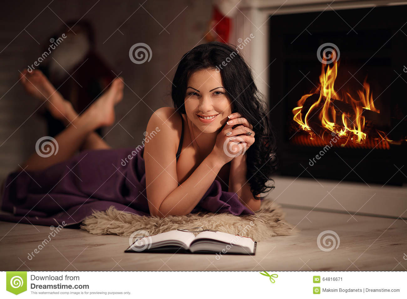 portrait of beautiful woman reading book by fireplace stock image