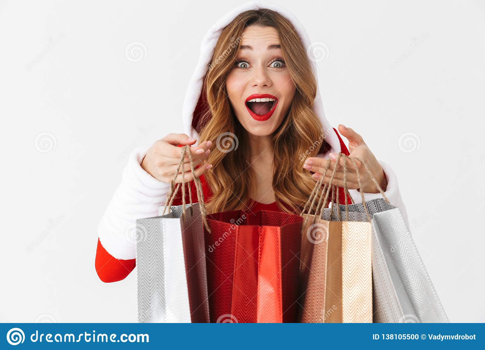Portrait of beautiful woman 20s wearing Santa Claus red costume smiling and holding colorful paper shopping bags with purchases,