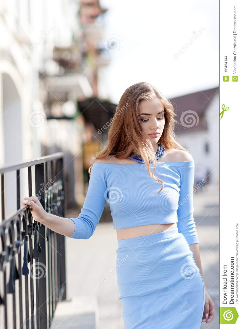 Portrait of a beautiful woman in a youth style on a city walk.