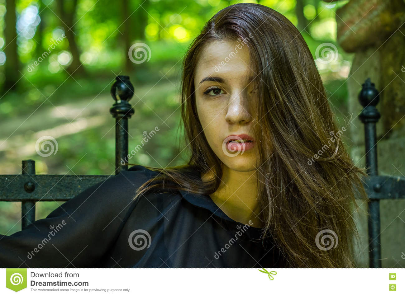 Portrait of a beautiful young and attractive teen girl with long hair near the steel gates of the destroyed stone castle in