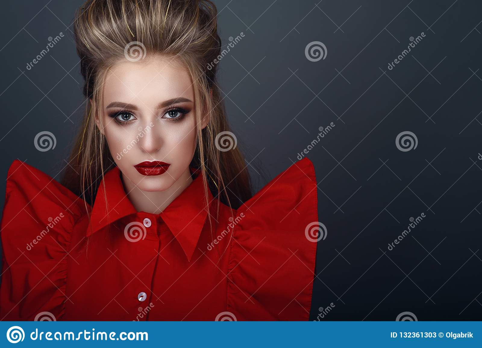 Portrait of beautiful young blond model with perfect provocative make up and stylish creative hairstyle wearing bright red blouse