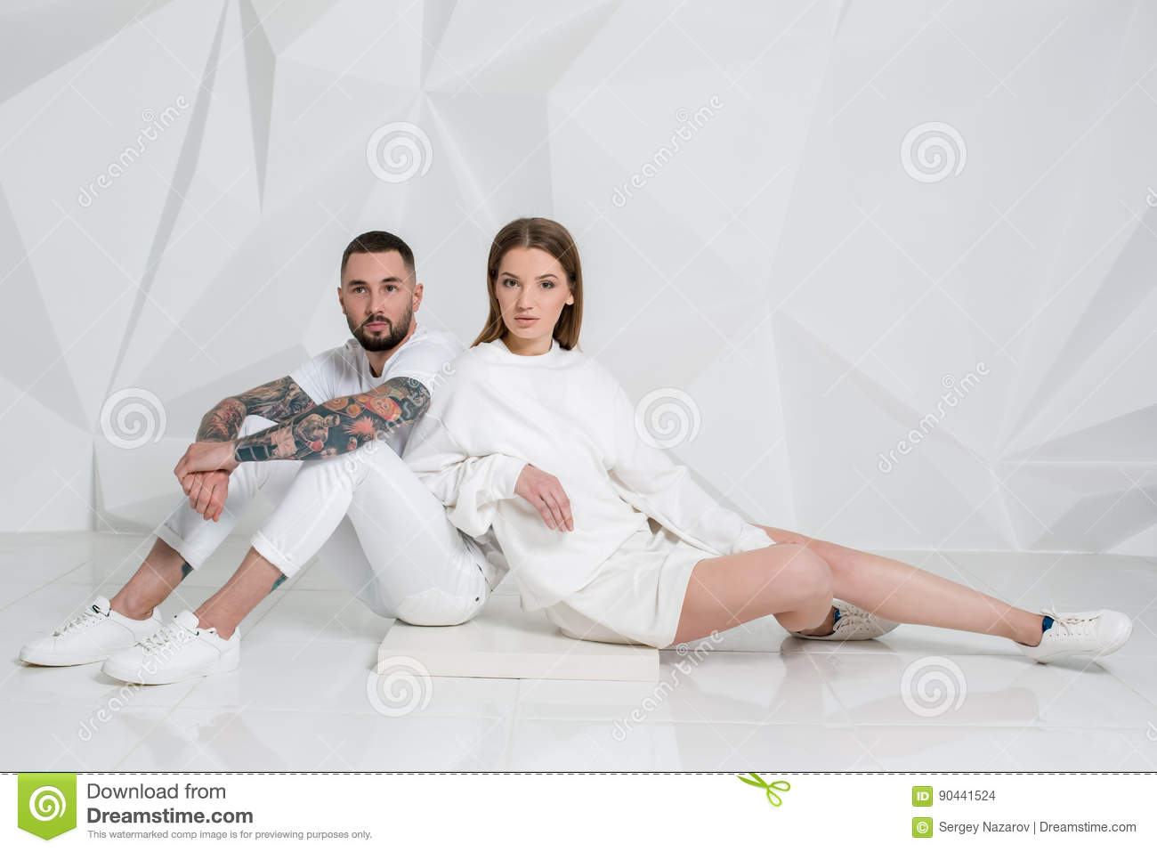 117ba72d48 Portrait of a beautiful young couple in love posing at studio over white  background. Man and women in white clothing