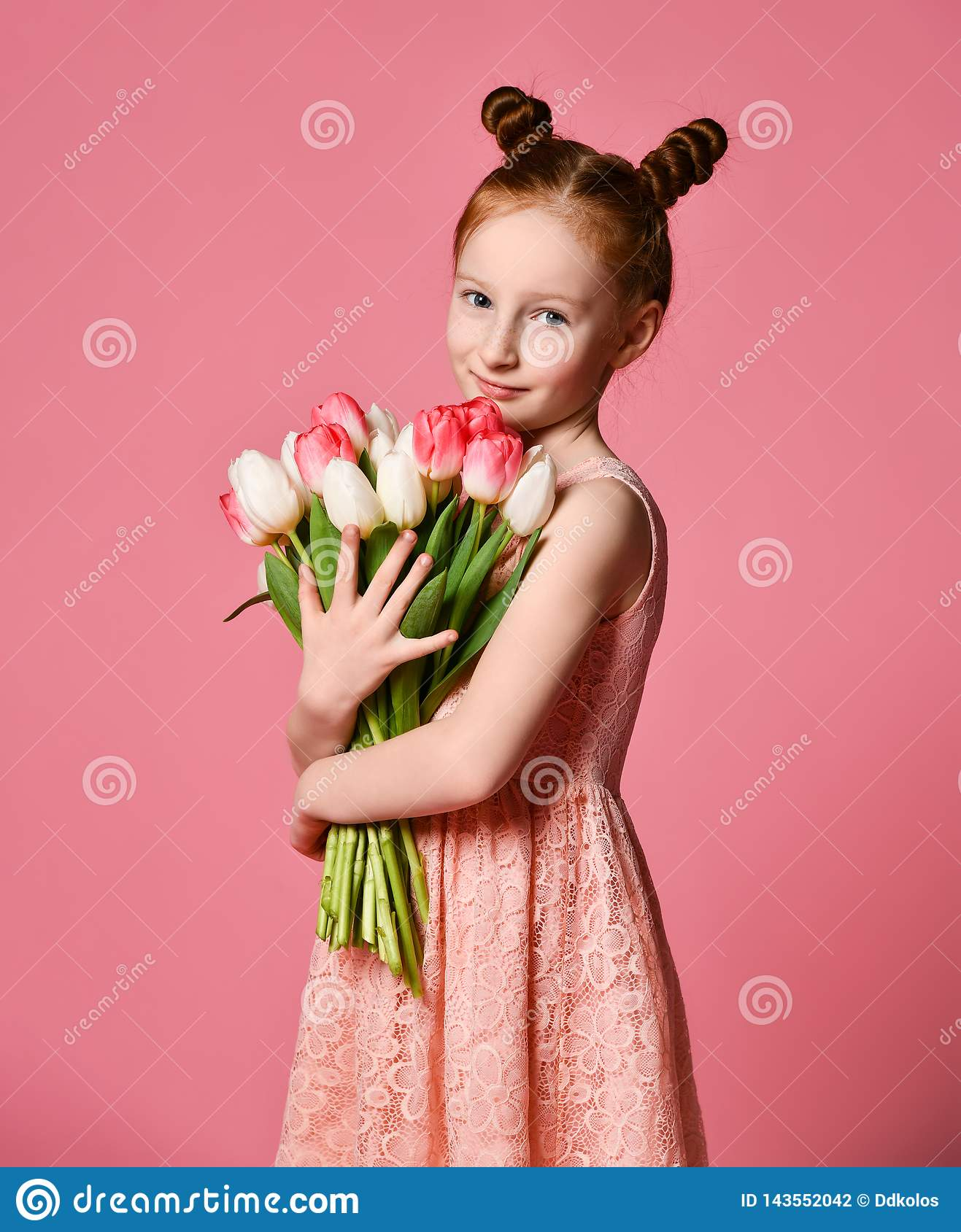 Portrait of a beautiful young girl in dress holding big bouquet of irises and tulips isolated over pink background