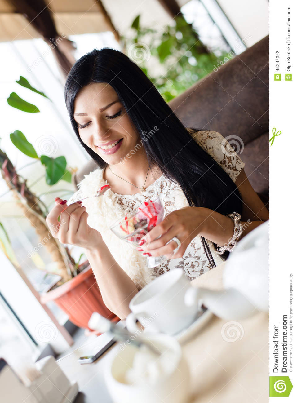 Portrait of beautiful young happy smiling woman having fun eating ice cream in coffee shop or restaurant