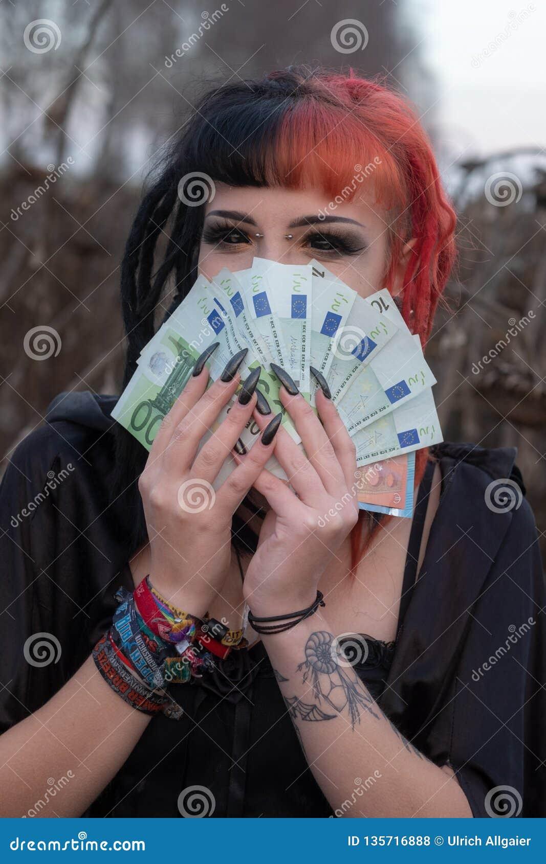Portrait of a beautiful young individual, eccentric woman, is enjoying many euro bills