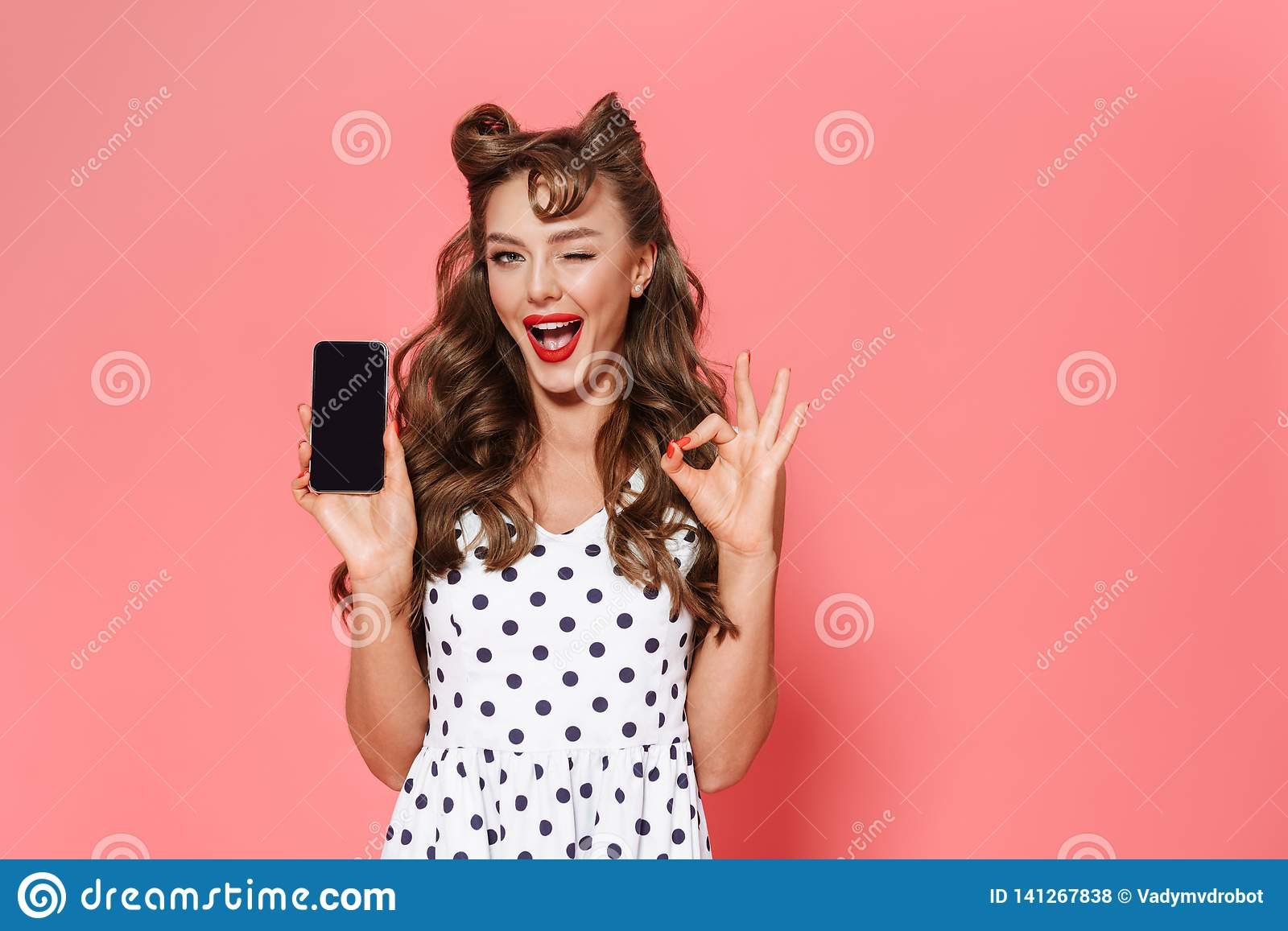 6bd788411 Portrait of a beautiful young pin-up girl wearing dress standing isolated  over pink background