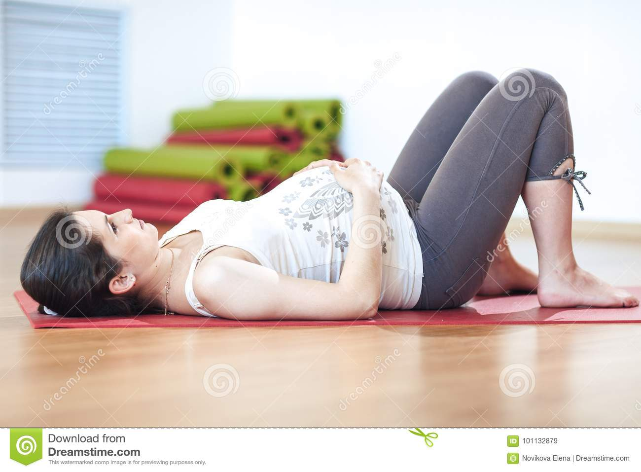 Portrait of a beautiful young pregnant woman doing exercises. Working out, yoga and fitness, pregnancy concept.