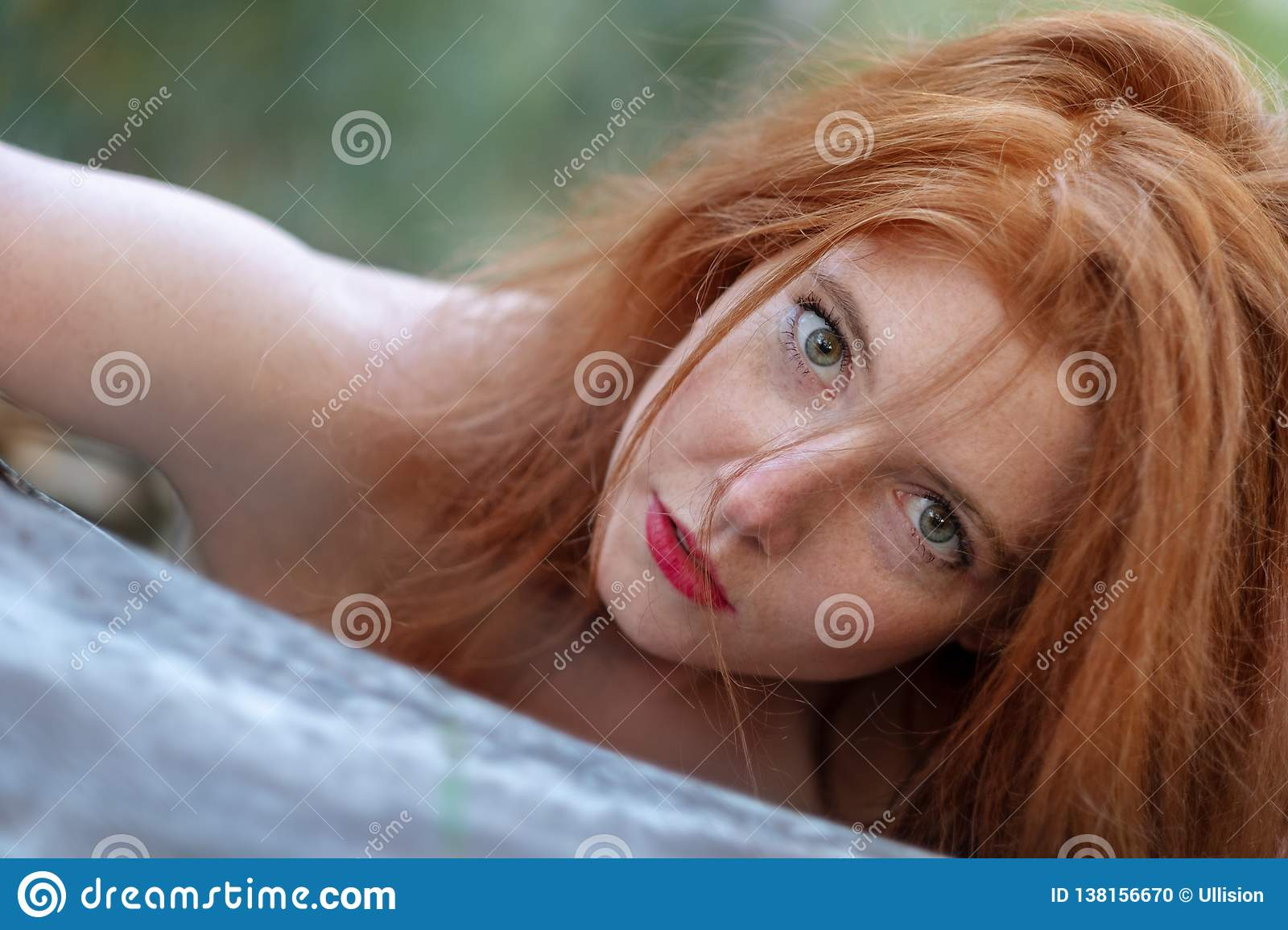 Portrait of a beautiful young red-haired woman with green eyes is sensually leaning against a fallen gray tree trunk
