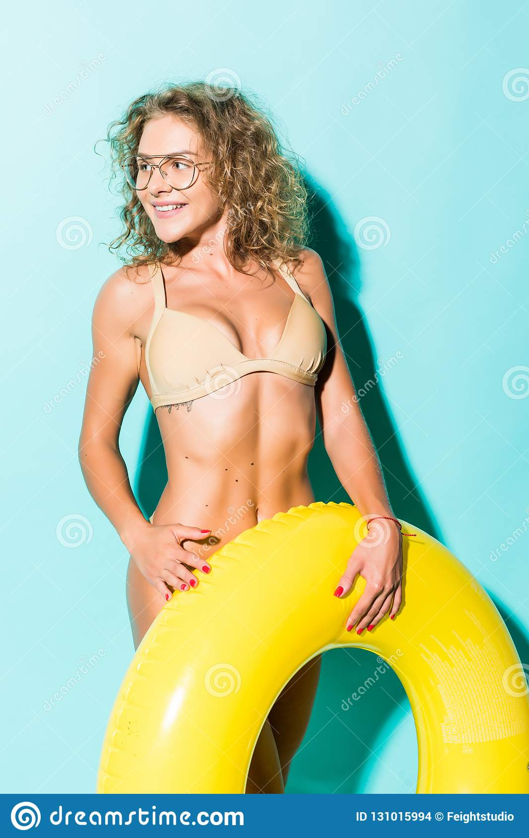 Portrait of beautiful young woman in bikini and glasses playing with inflatable yellow float isolated on blue background