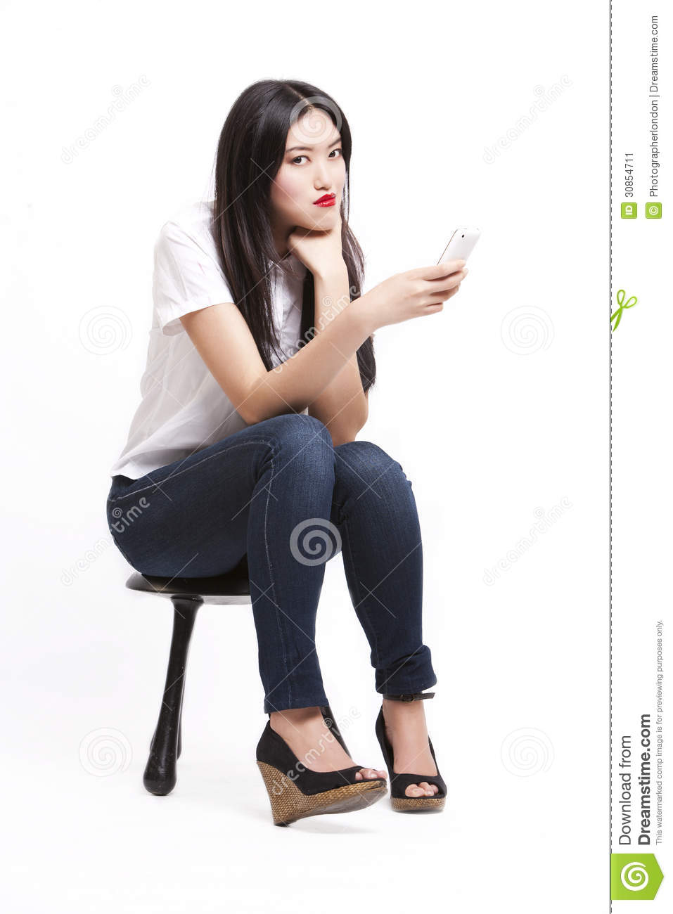 Portrait Of Beautiful Young Woman In Casuals Sitting On