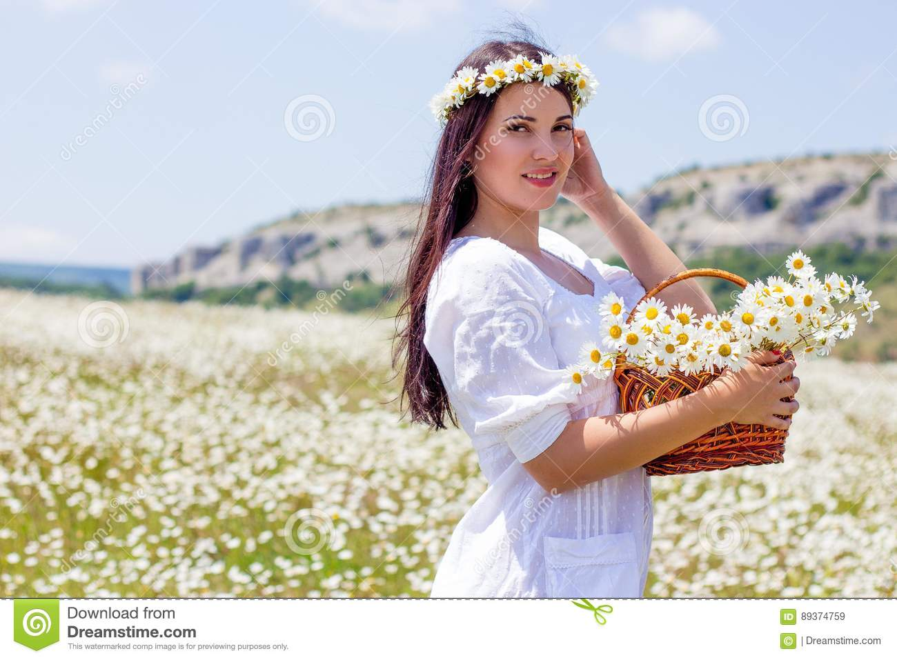 Portrait of a beautiful young woman in chamomile field. Happy girl collecting daisies. A girl resting in a field of chamomile. S