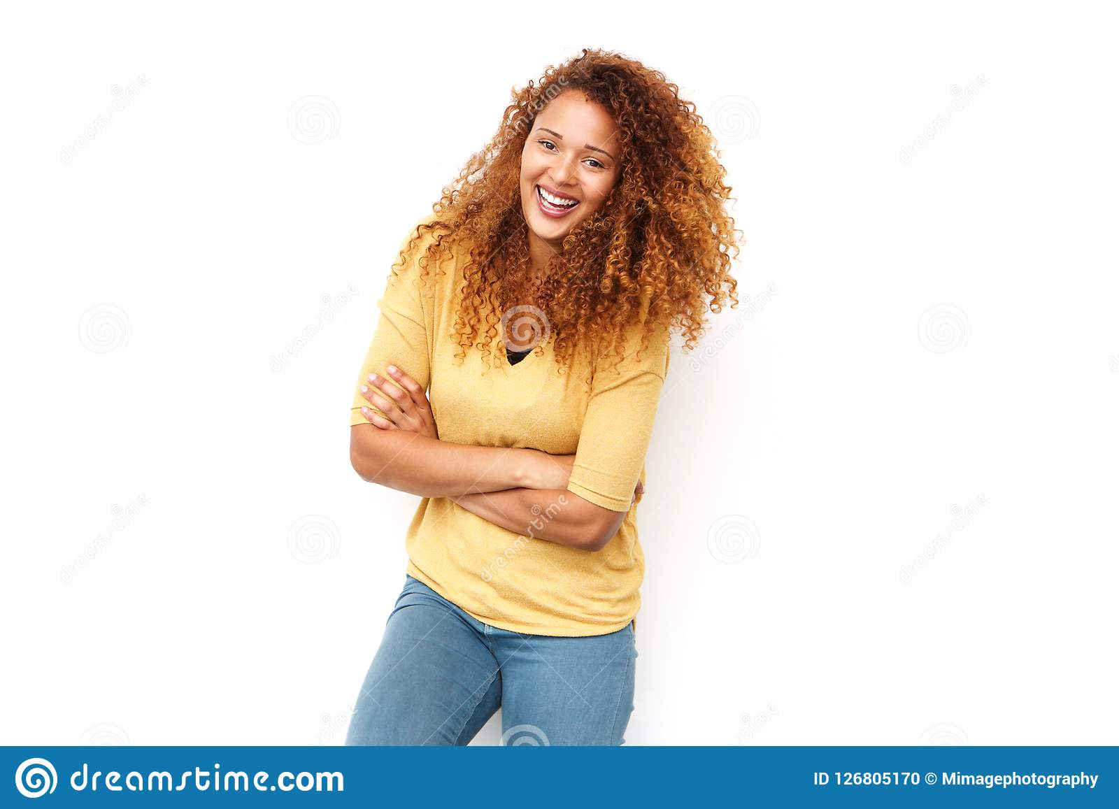 Beautiful young woman with curly hair laughing with arms crossed against white background