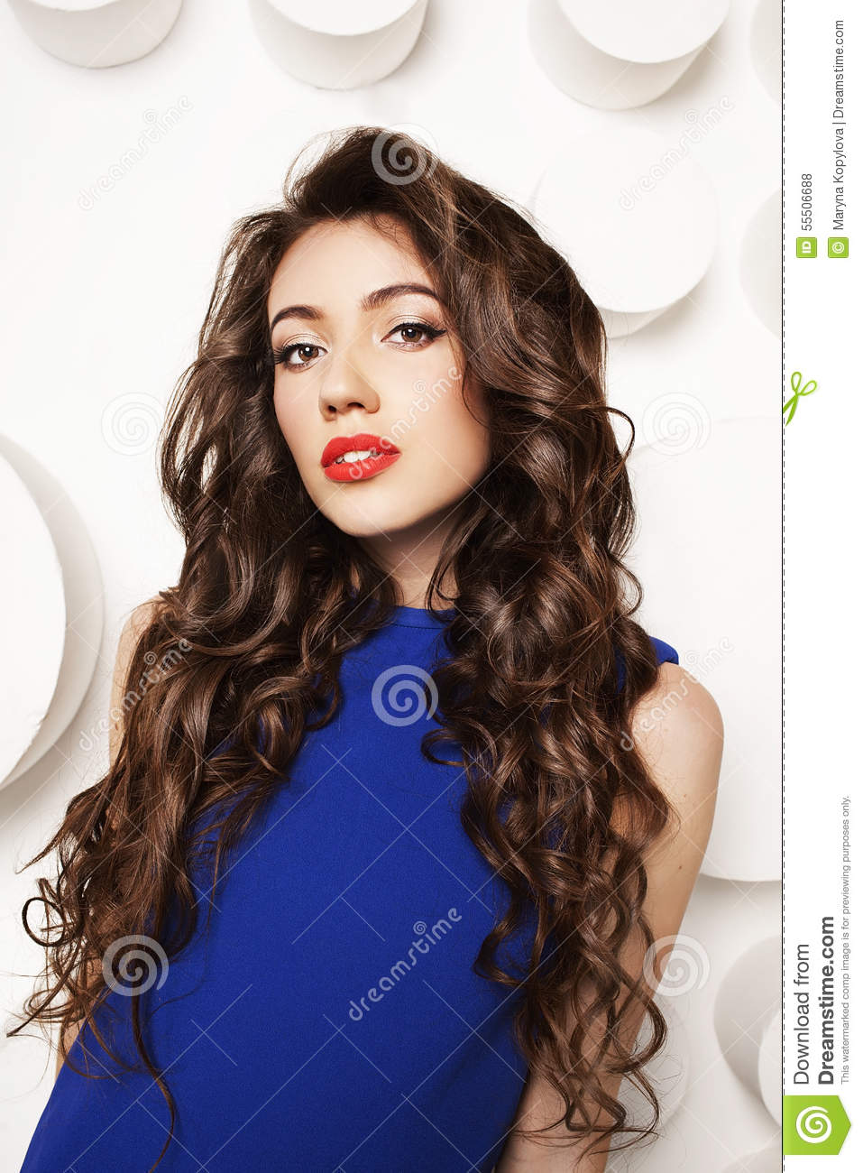 Portrait Of Beautiful Young Woman With Curly Long Brown Hair In Blue