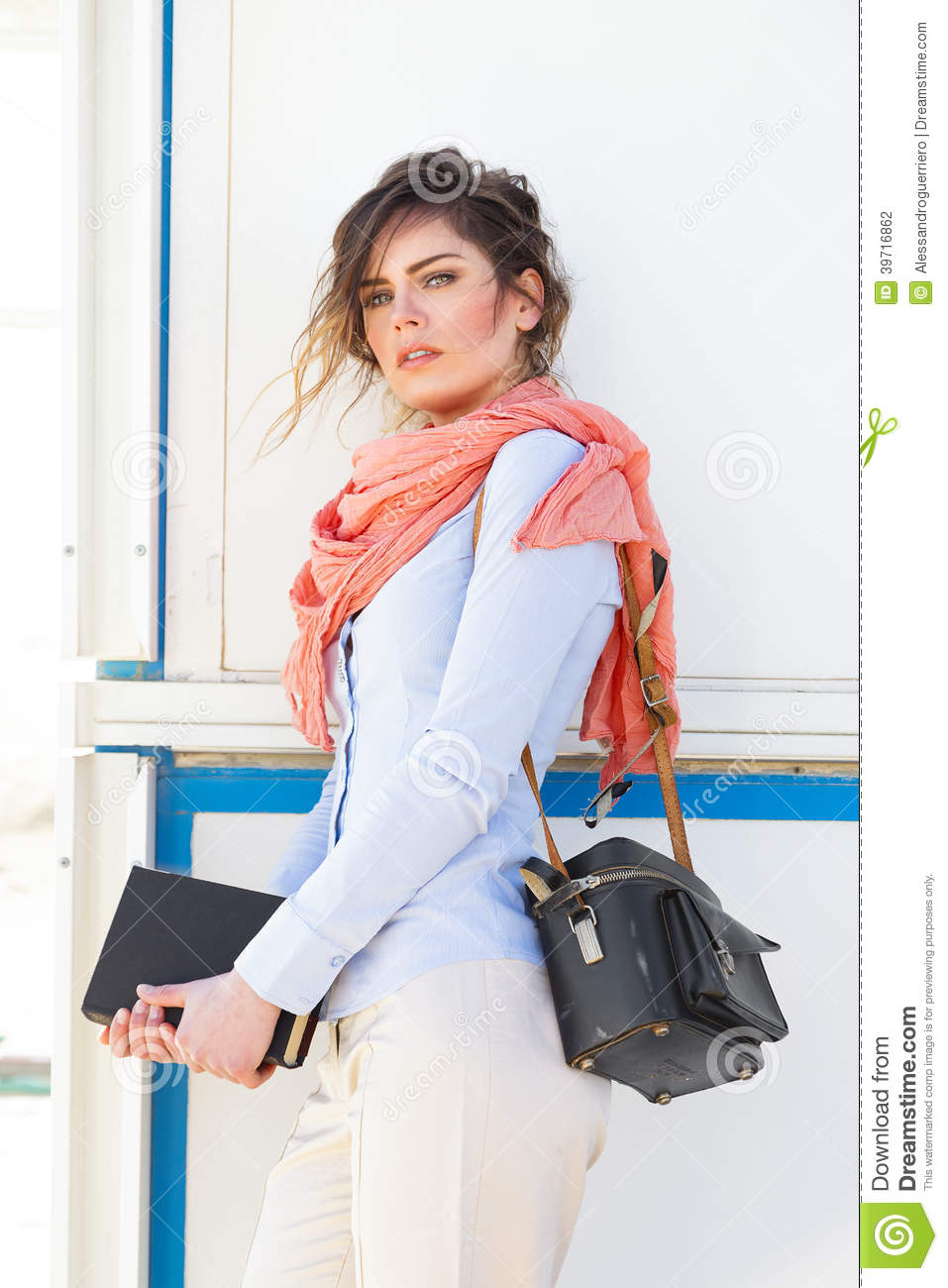 Portrait Of Beautiful Young Woman Holding A Book And Camera