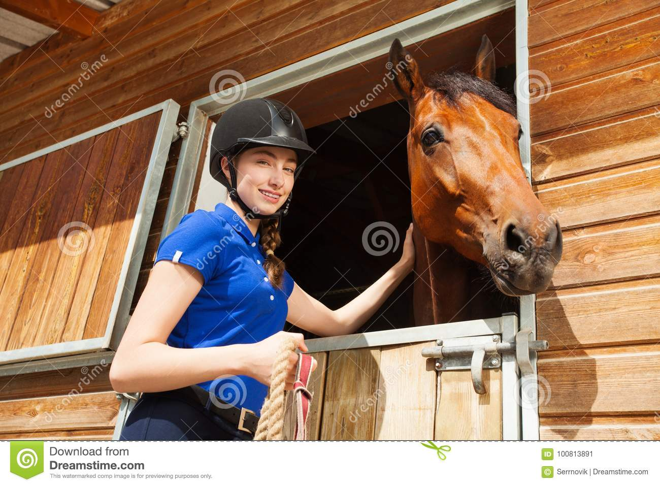 Happy jockey girl stroking horse at riding stable