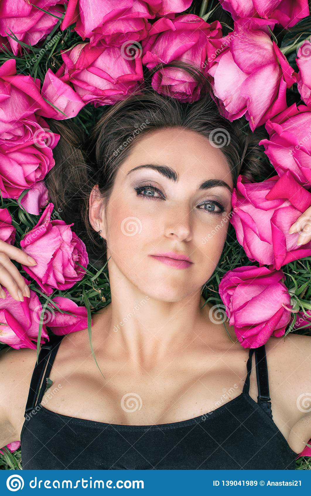 Portrait of a beautiful young woman, she is lying on the grass surrounded by roses. Festive background.