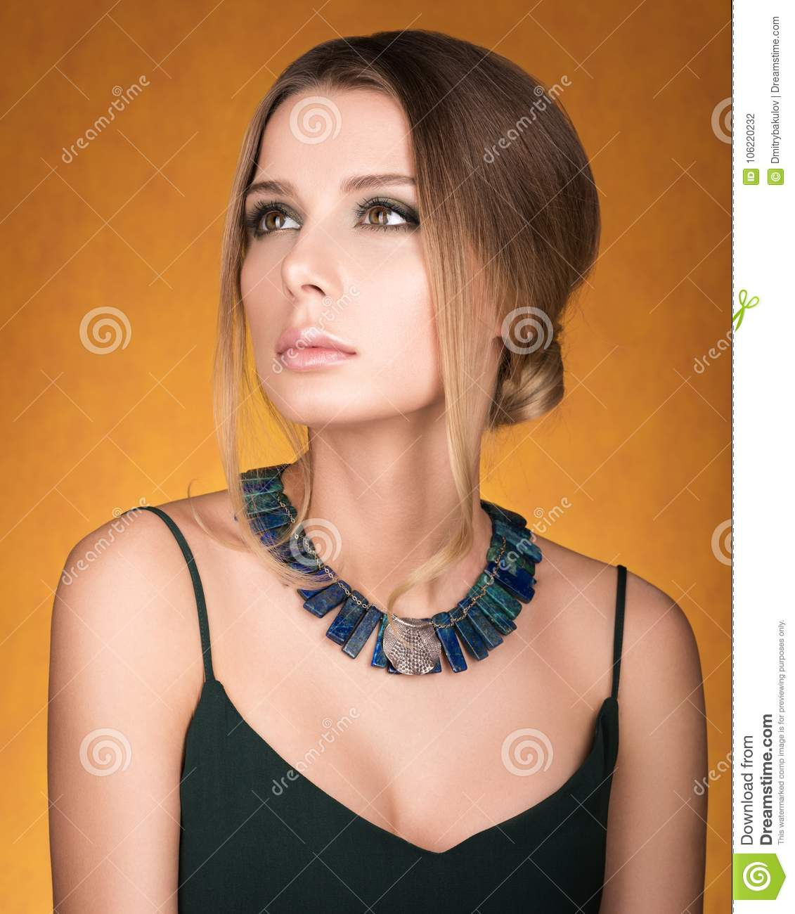 Portrait Of Beautiful Young Woman With A Necklace On Her Neck
