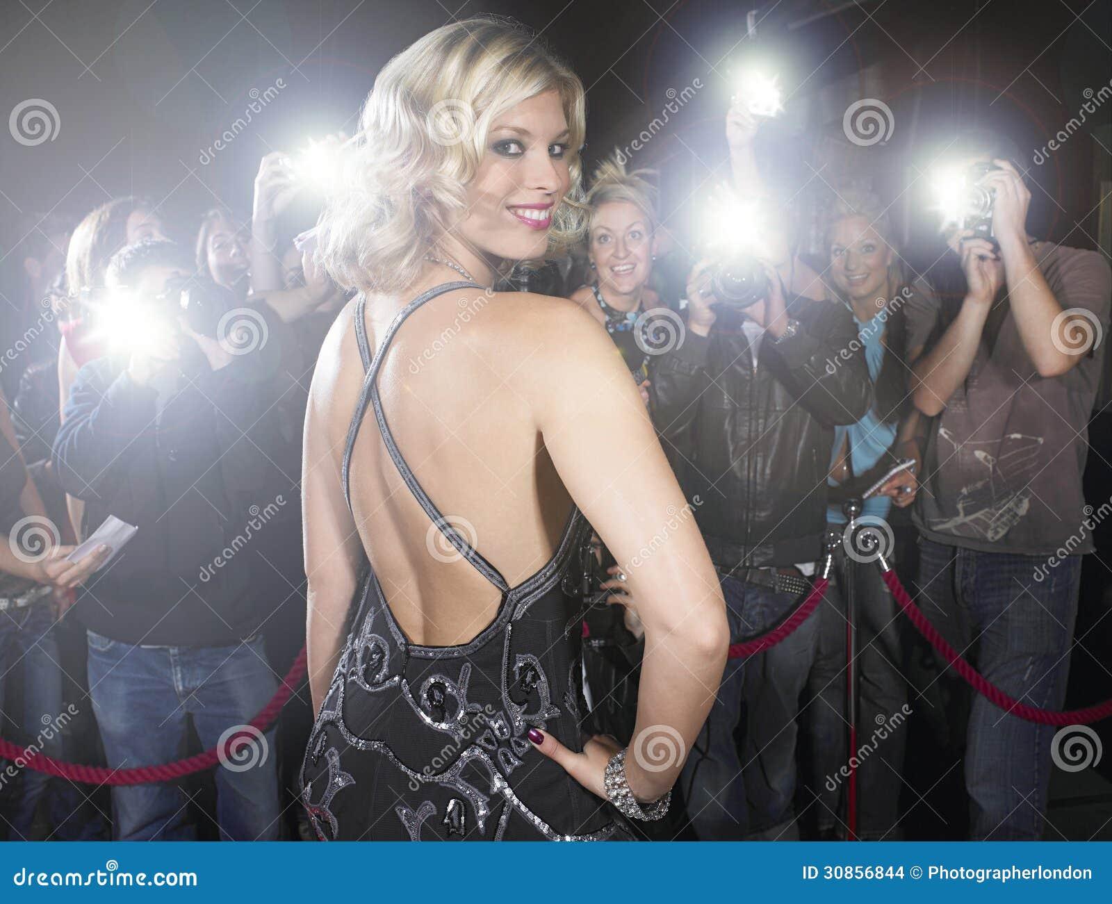 Portrait of beautiful young woman posing for paparazzi