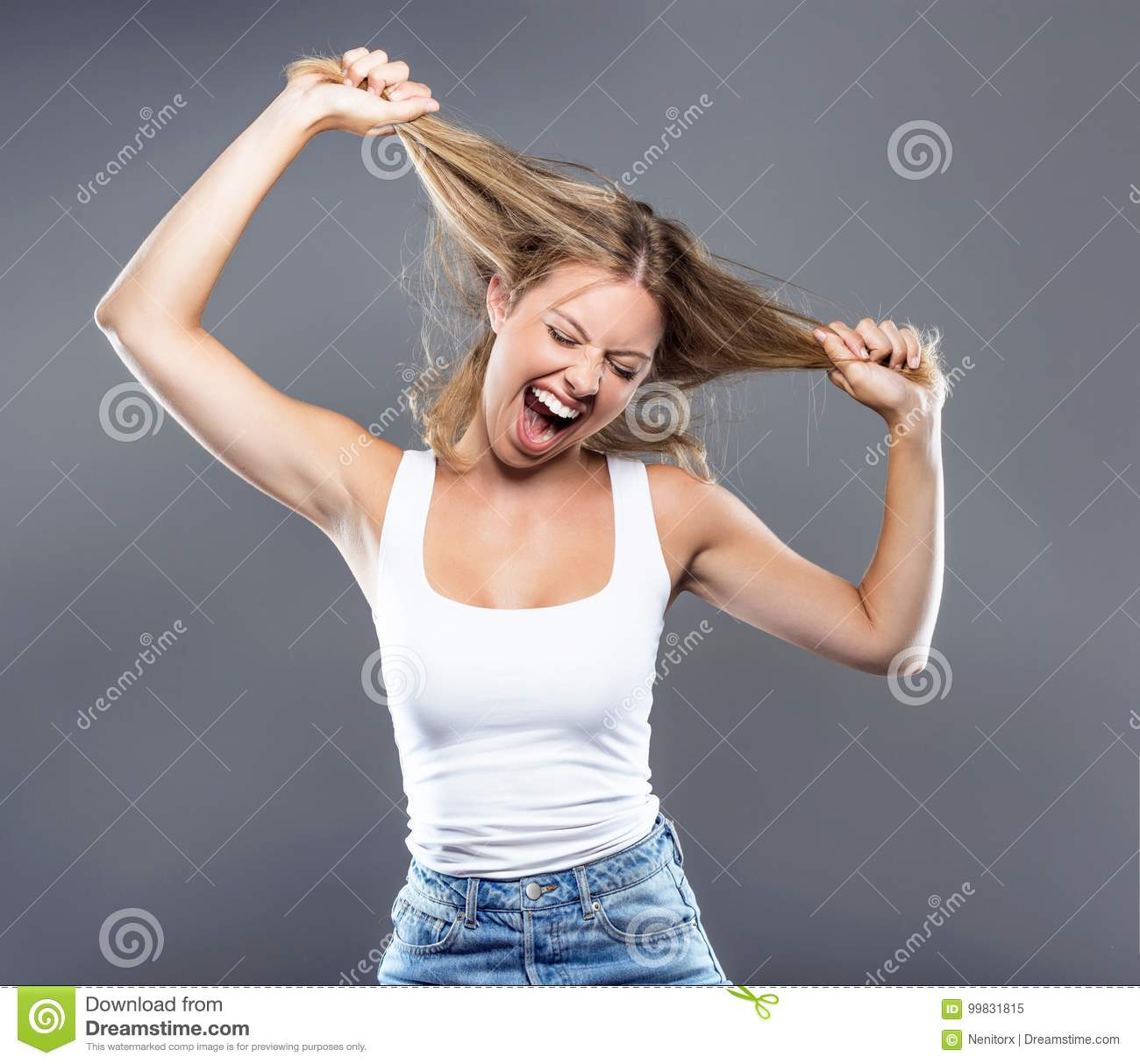 Beautiful young woman pulling her hair over gray background.