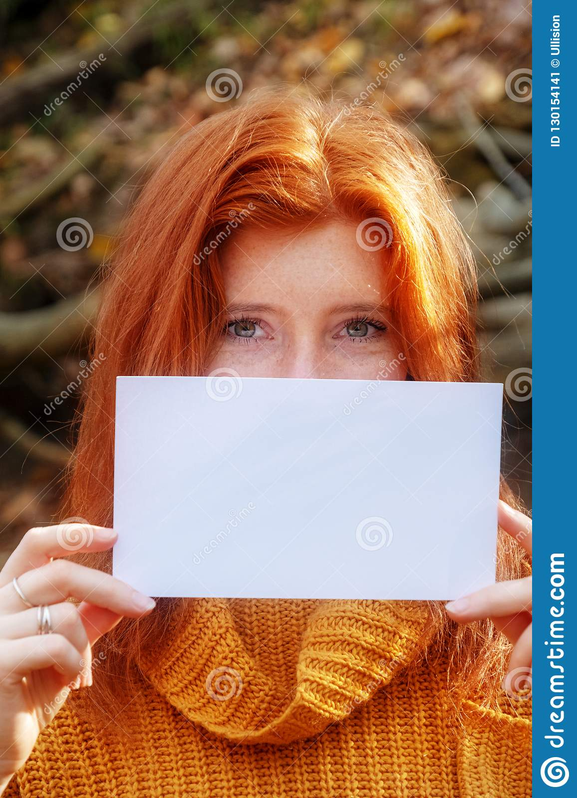 Portrait of beautiful young woman with red hair, ginger, in orange sweater smiling holding a blank blank paper in both hands