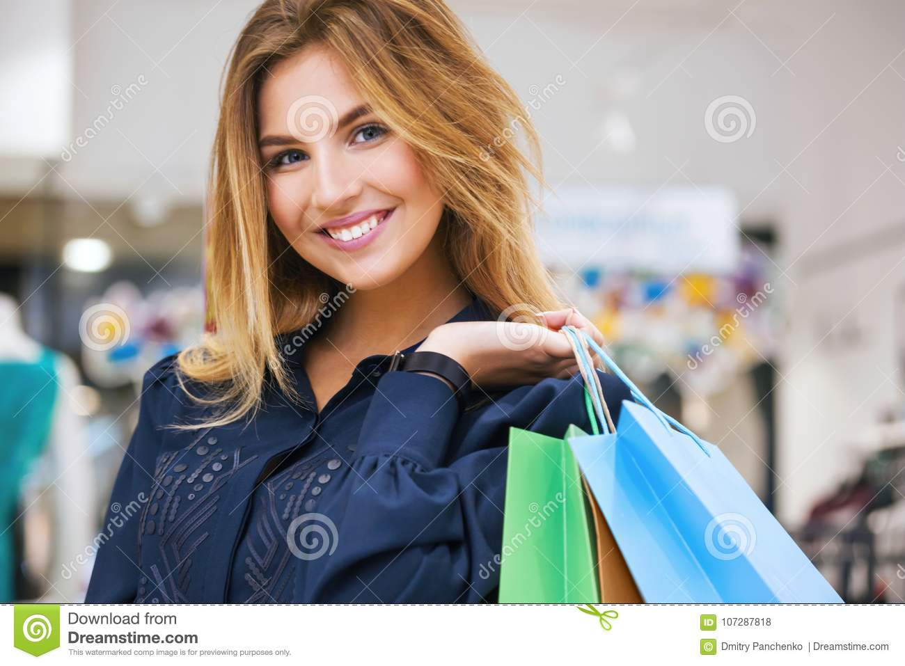 b67e6c1a25 Portrait of beautiful young woman with shopping bags going out on a shopping  spree.