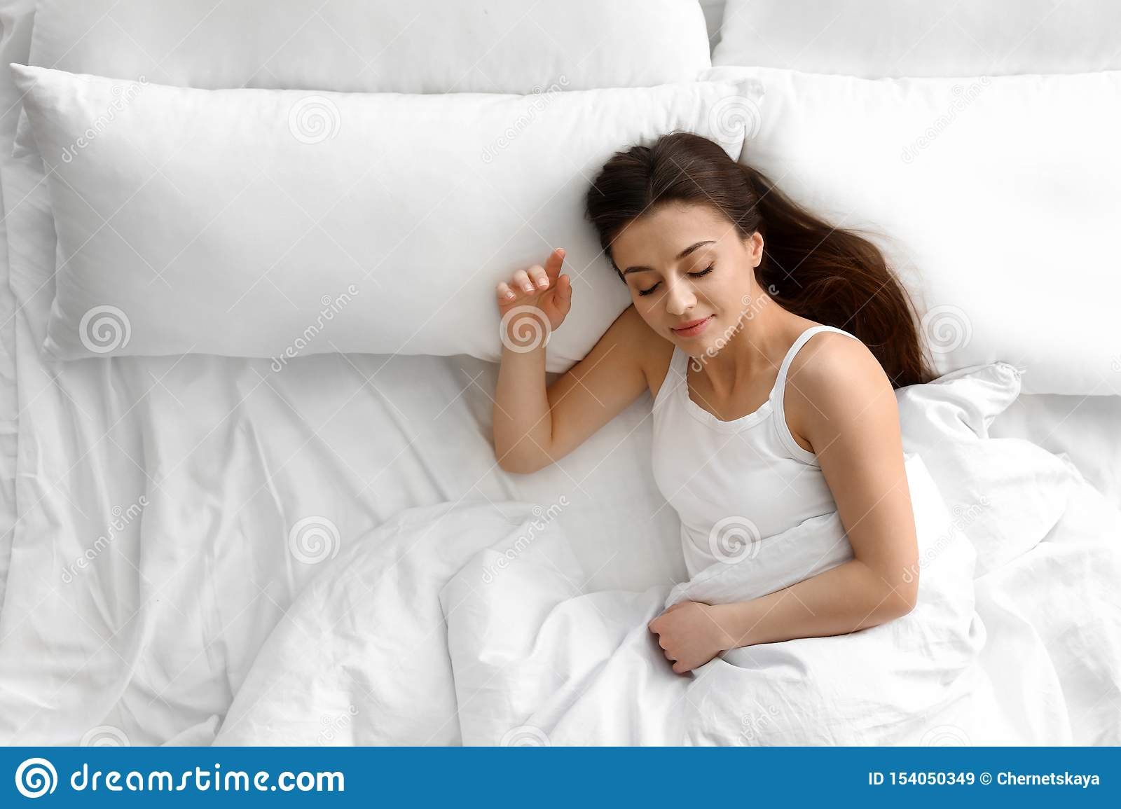 Portrait of beautiful young woman sleeping in large bed, above