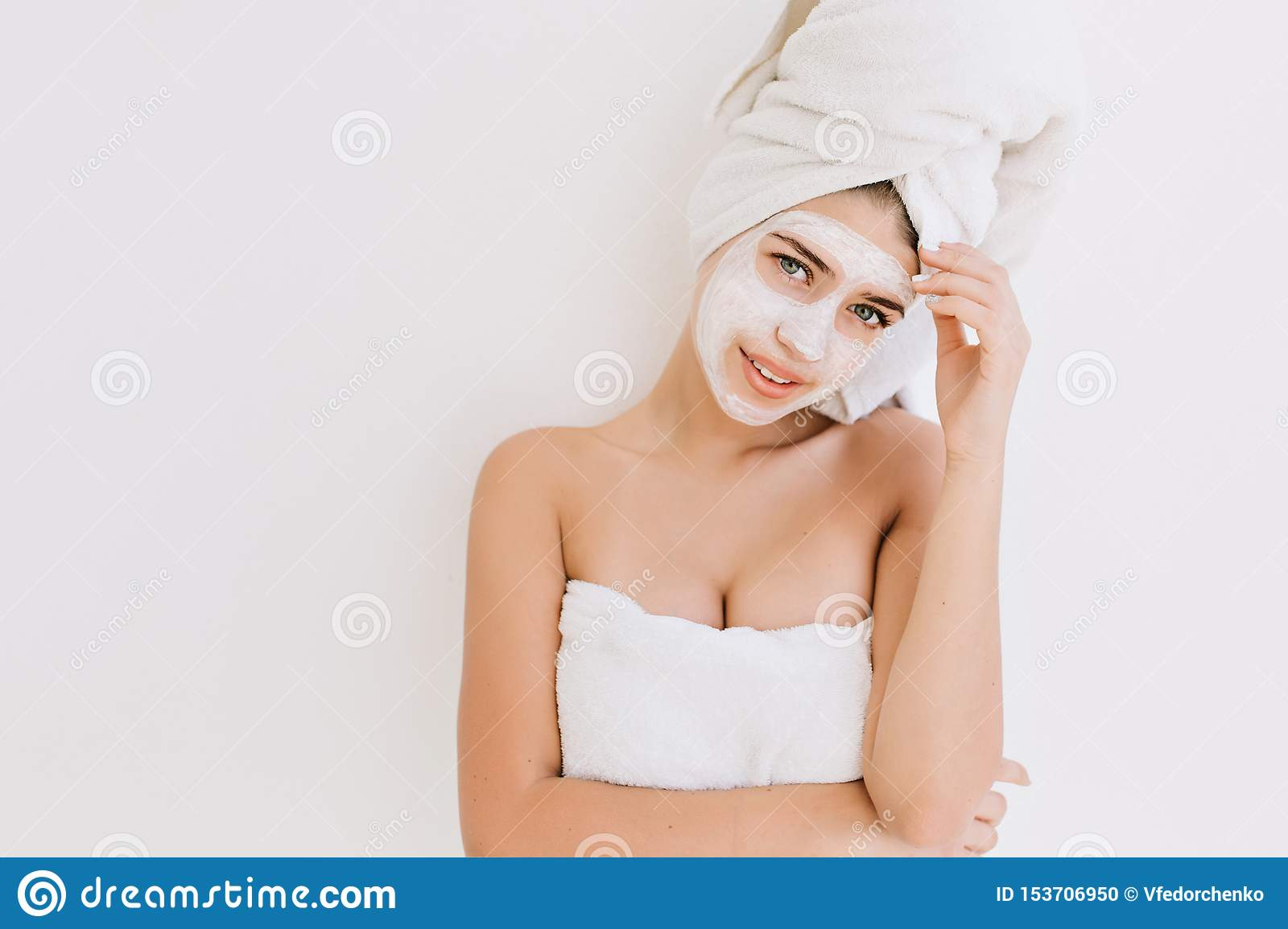 Portrait of beautiful young woman with towels after take bath make cosmetic mask on her face. Rejuvenation, cosmetology