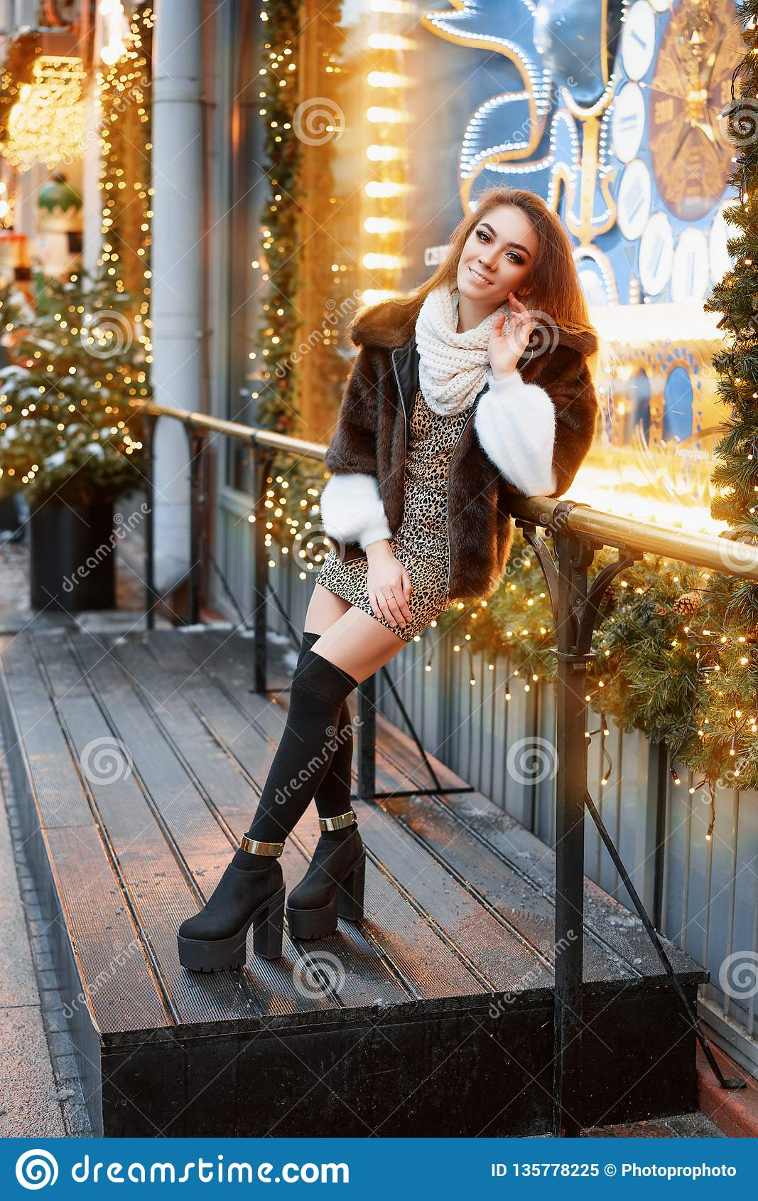 Portrait of a beautiful young woman who poses on the street near the elegantly decorated Christmas window, festive mood
