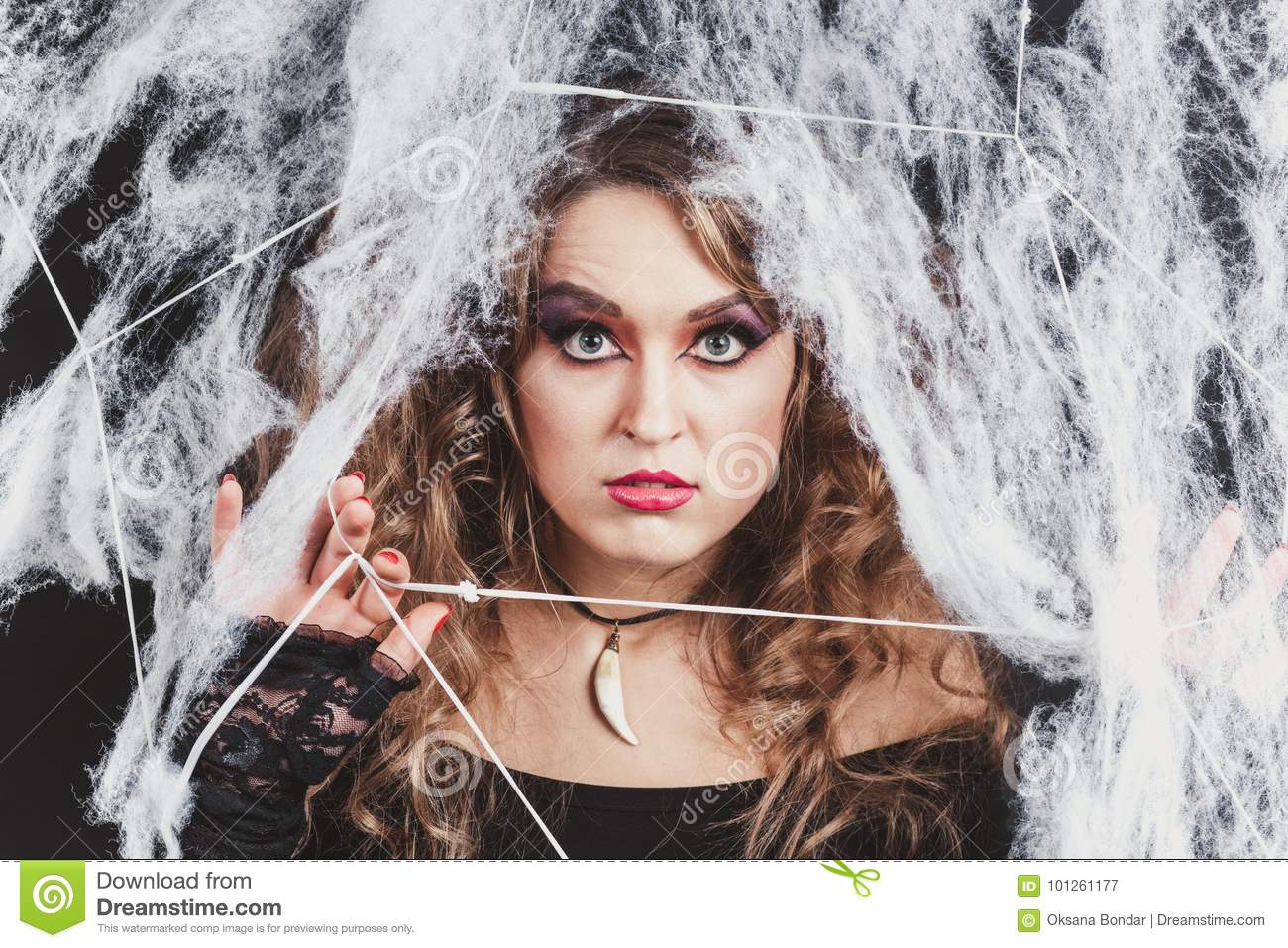 Portrait of Beauty Witch girl caught in a spider web. Fashion Art design. Beautiful Gothic model girl with