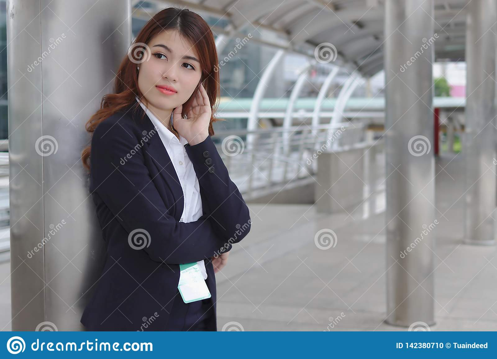 Portrait of beauty young Asian businesswoman in suit standing and looking at far away. Thinking and thoughtful business concept