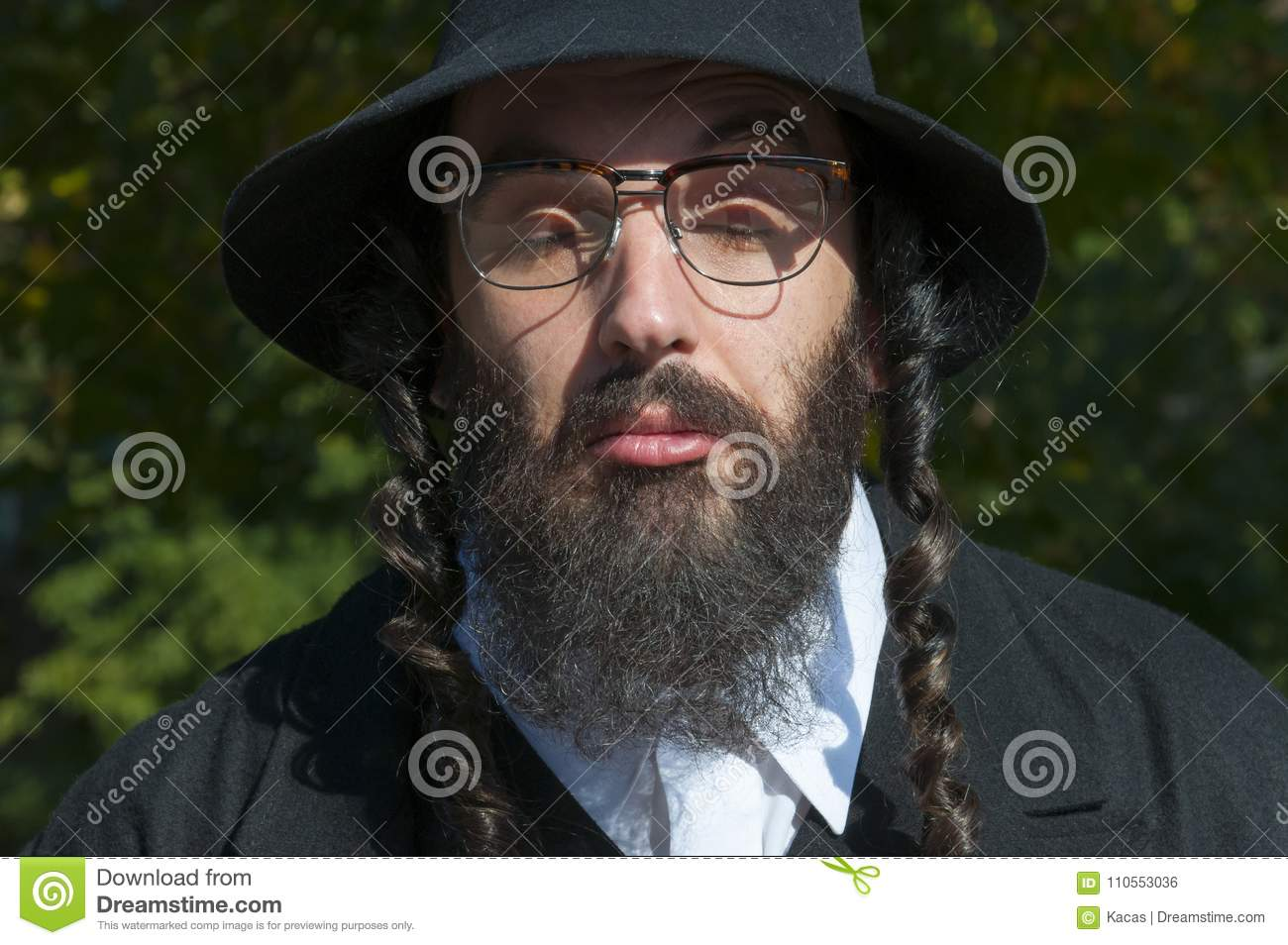 b6b657ad566c Outdoor sunny portrait of bewildered closed eyes young traditional orthodox  Jewish man with black beard and hat wearing eyeglasses