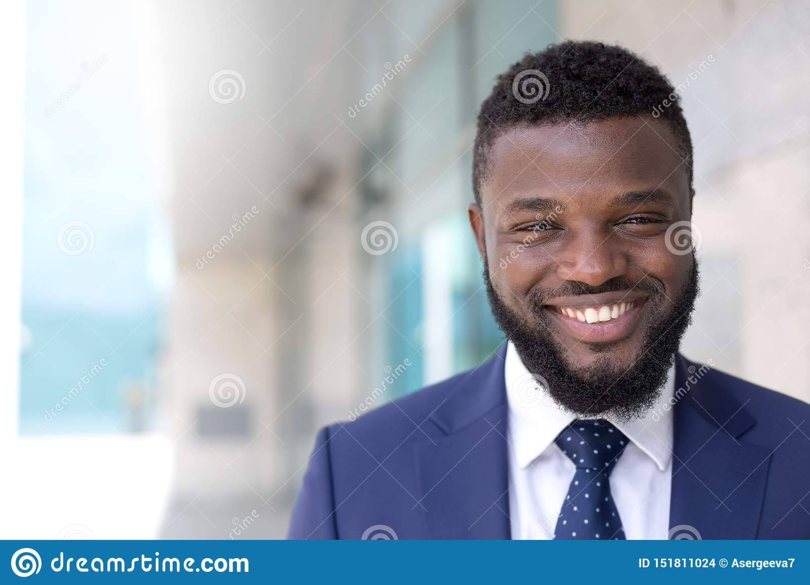Portrait of black smiling businessman looking at camera in an urban setting. Copy space