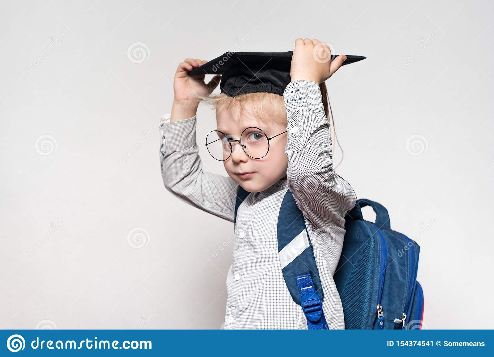 Portrait of a blond boy in glasses, an academic hat and a schoolbag on a white background. School concept