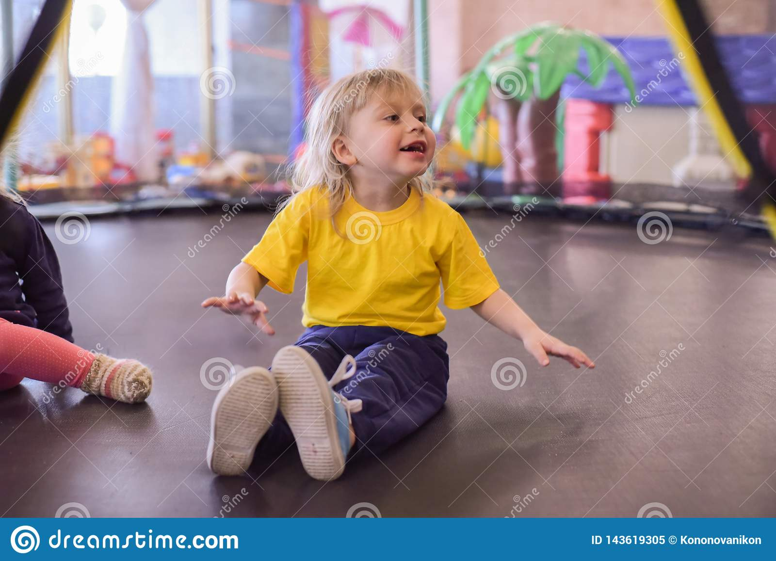 Portrait of a blond boy in a yellow t-shirt. The child smiles and plays in the children`s playroom. The child jumps on the