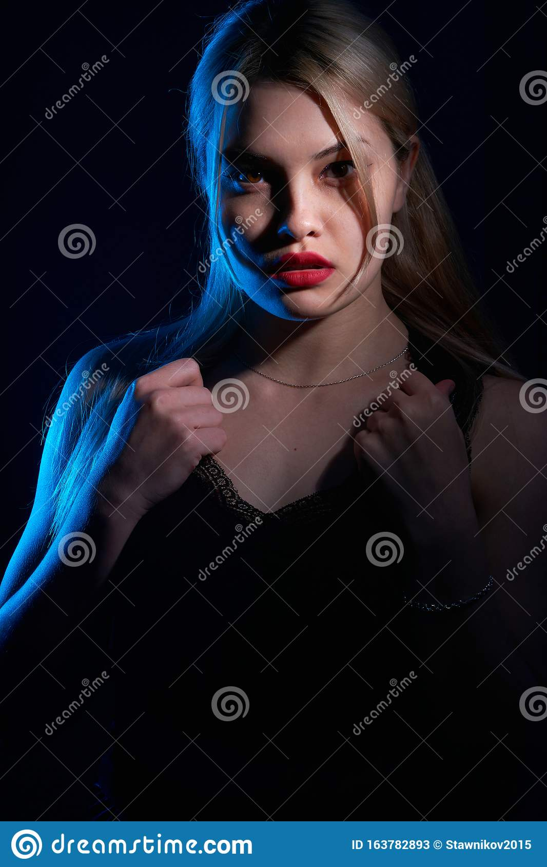Portrait Of A Beautiful Girl With Red Lips On A Blue Background